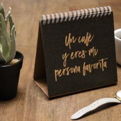 Flip-book con cactus sobre mesa de madera