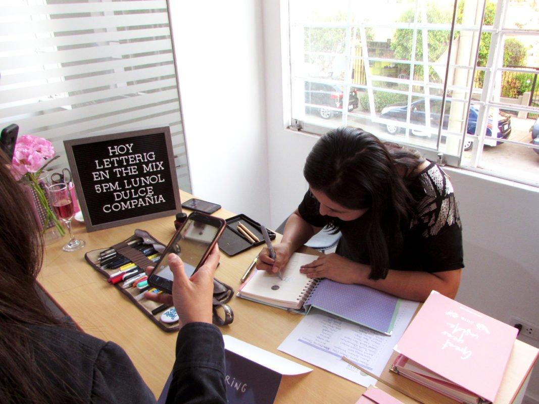 AgenDATE Lunol haciendo lettering con letrero